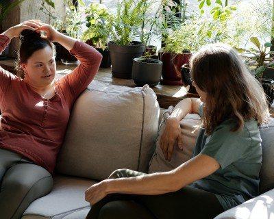 Two women talking on a sofa