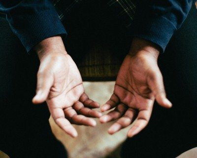 A person with their hands open - praying