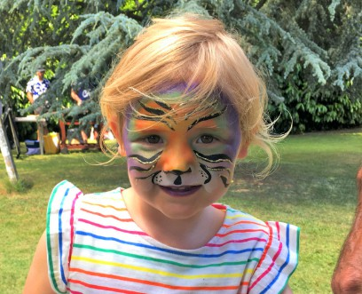 A young girl with a her face painted from our summer fete